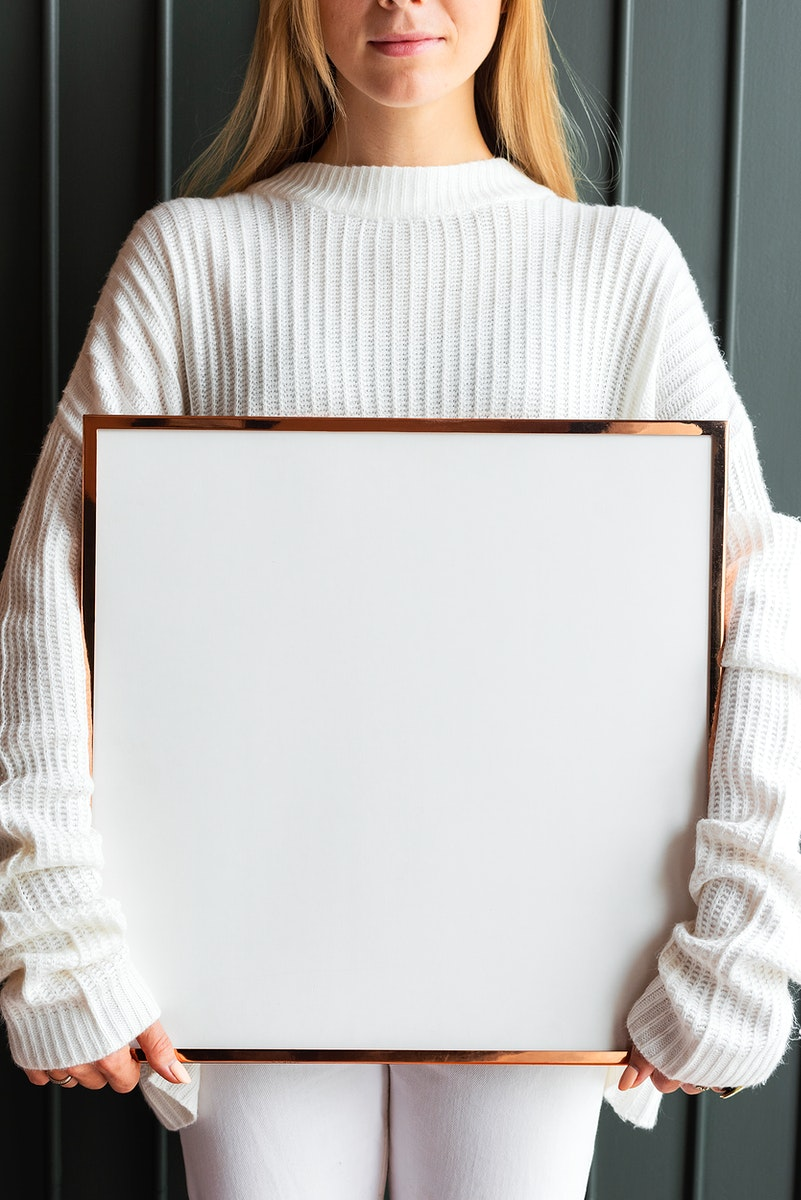 Woman in a white sweater holding a wooden frame mockup