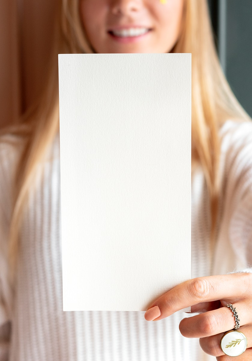 Woman in a white sweater holding a card mockup