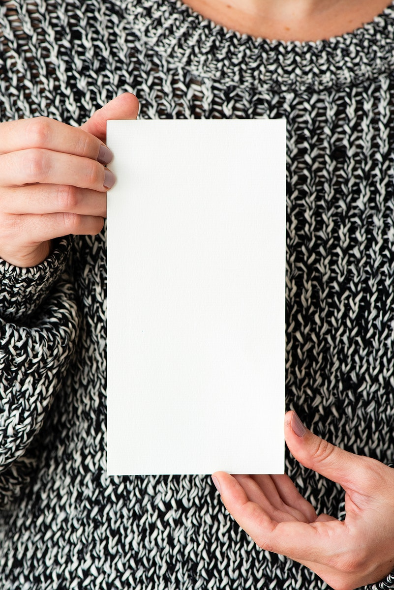Woman in a gray sweater holding an earth tone card mockup