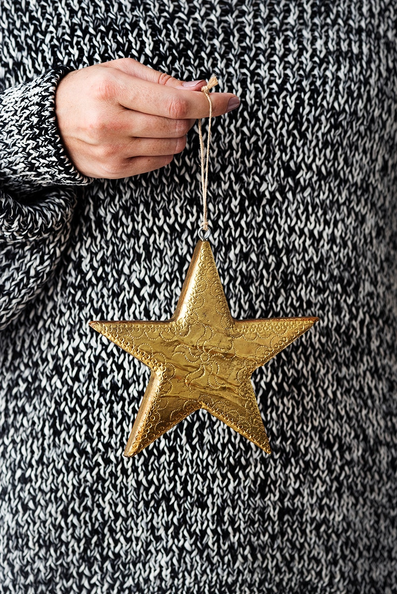 Woman holding a glittery gold star Christmas ornament