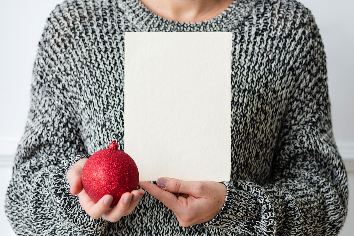Woman holding a red bauble next to a white card mockup