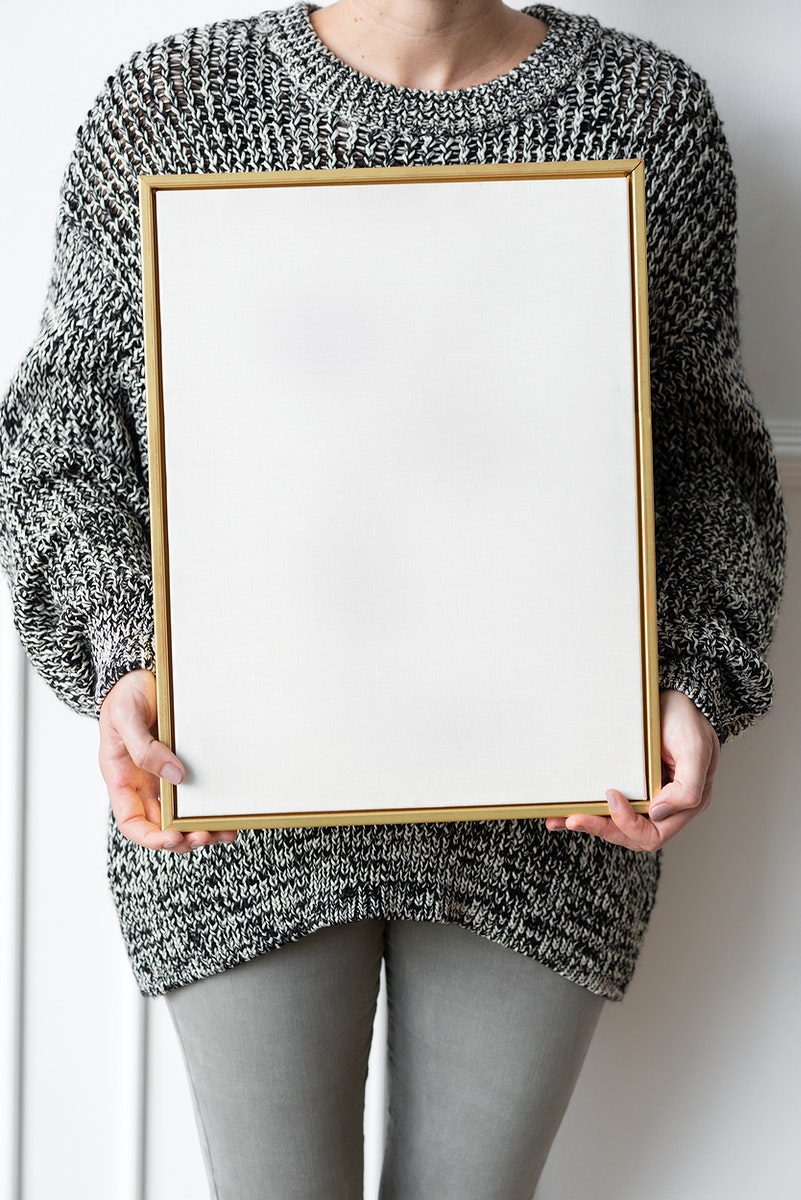 Woman in a black sweater holding a wooden frame mockup