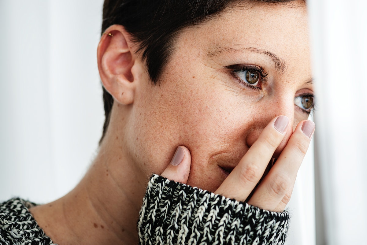 Woman in a gray sweater cover her mouth with fingers