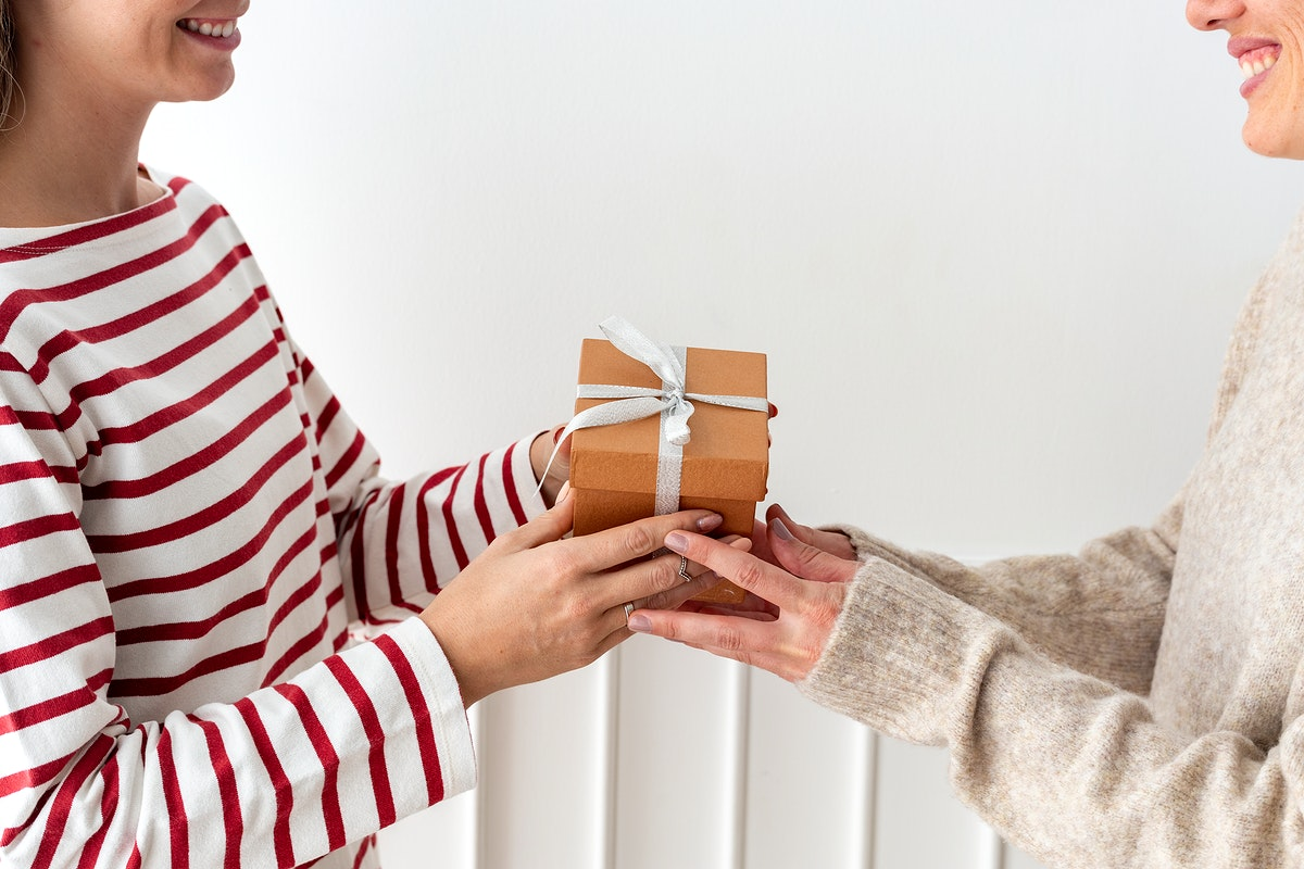 Blond girl giving a Christmas present to her friend