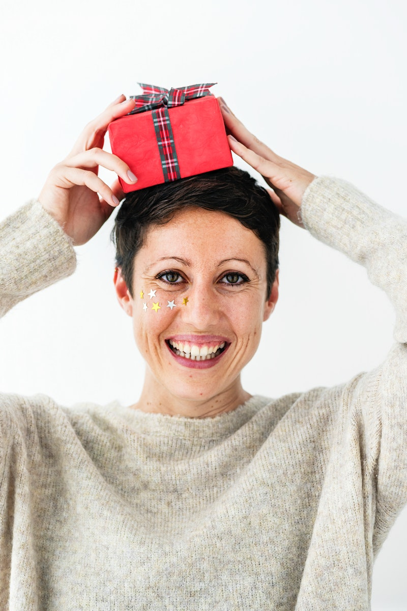 Woman putting a red present on her head