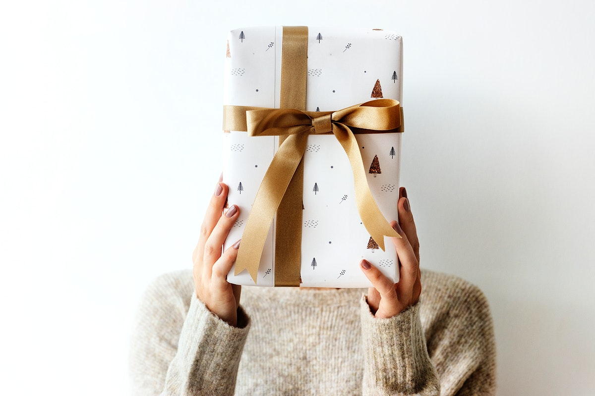 Woman covering her face with a white present