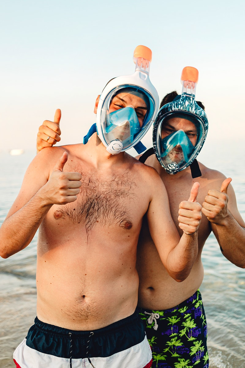 Men wearing full face snorkel mask standing at the beach