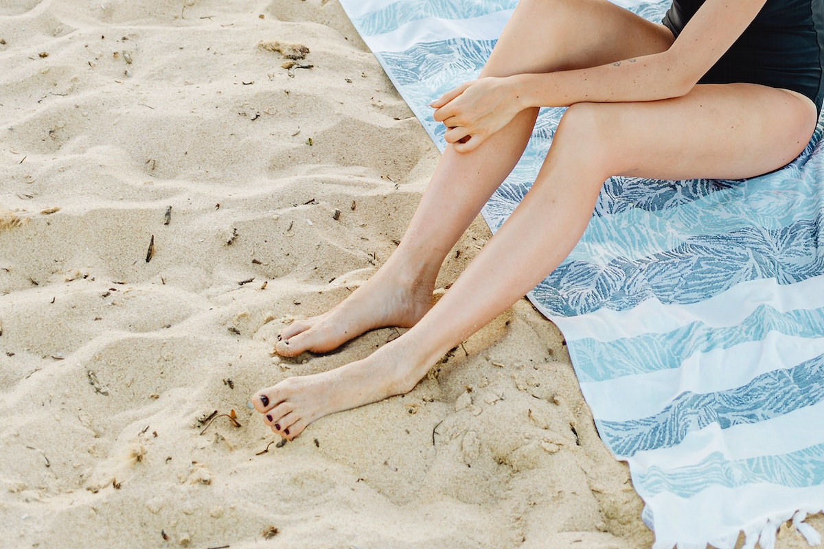 Girl in a blank swimsuit sitting on a striped towel at the beach