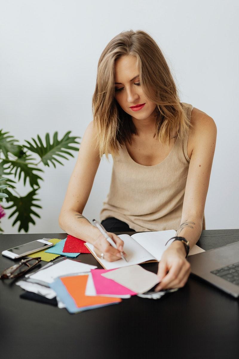 Female fashion designer writing on her notebook