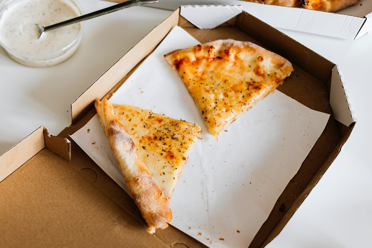 Two slices of cheese pizza in a box