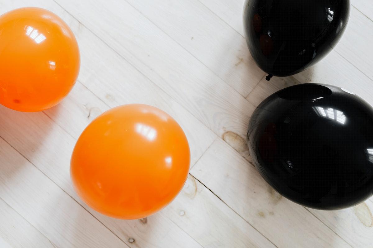 Orange and black balloons on the white wooden floor