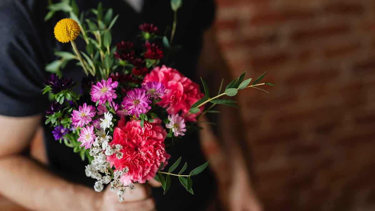 Man holding a bouquet of flowers