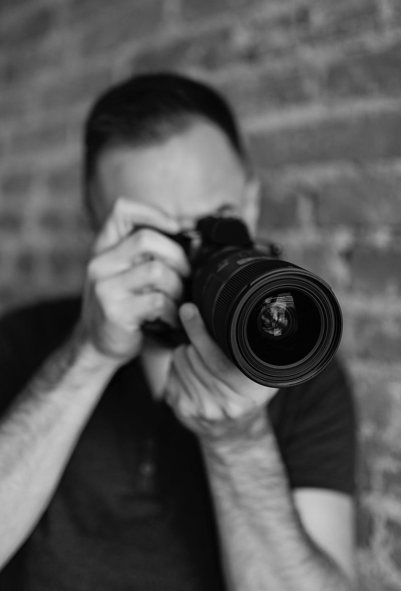 Male photographer taking a photo with his DSLR camera grayscale