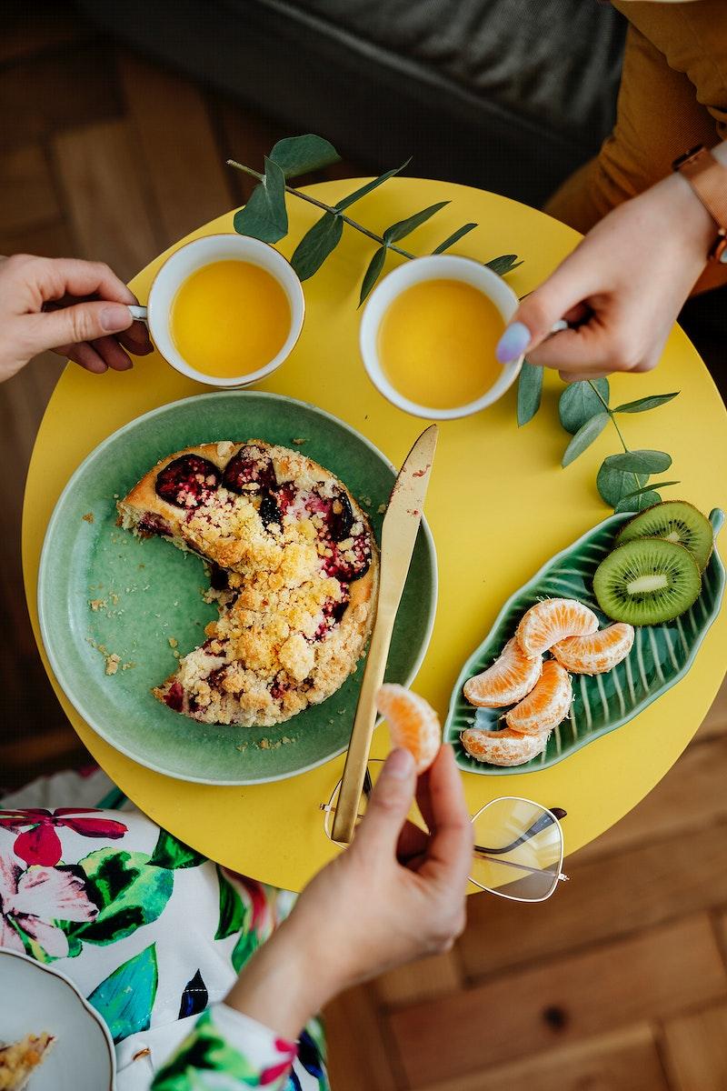 Women having tea with plum crumble pie