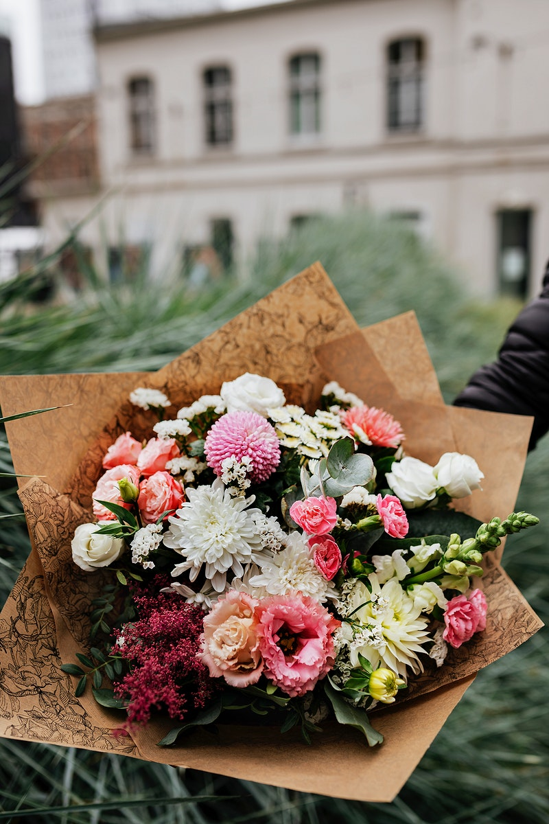 Man holding a bouquet of colorful flowers