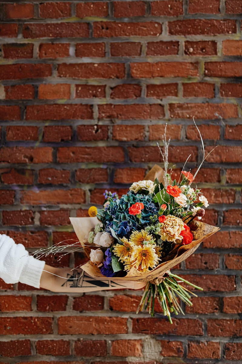 Bouquet of colorful flowers in front of brick wall