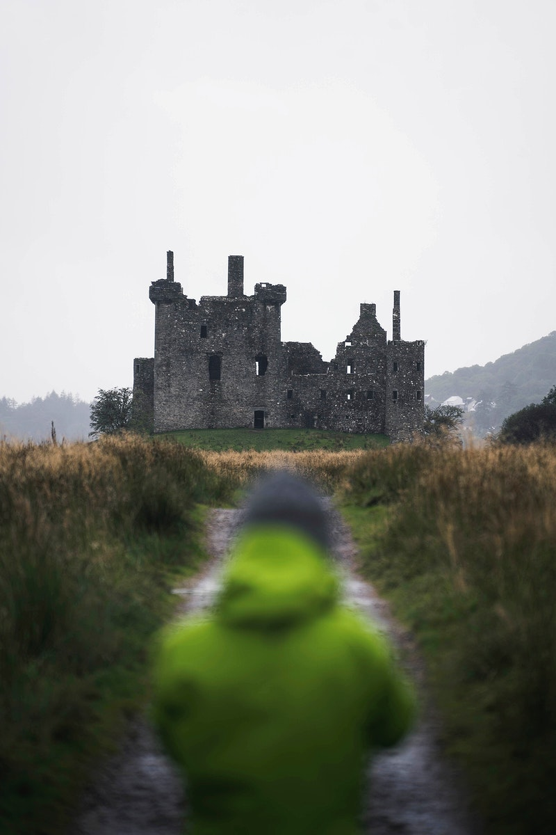 Rear view of a woman in front of Kilchurn Castle, Scotland