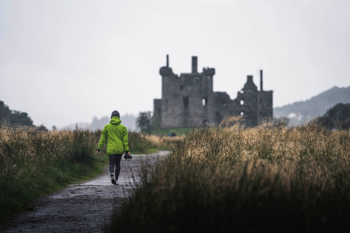 Rear view of a female photographer in front of Kilchurn Castle, Scotland