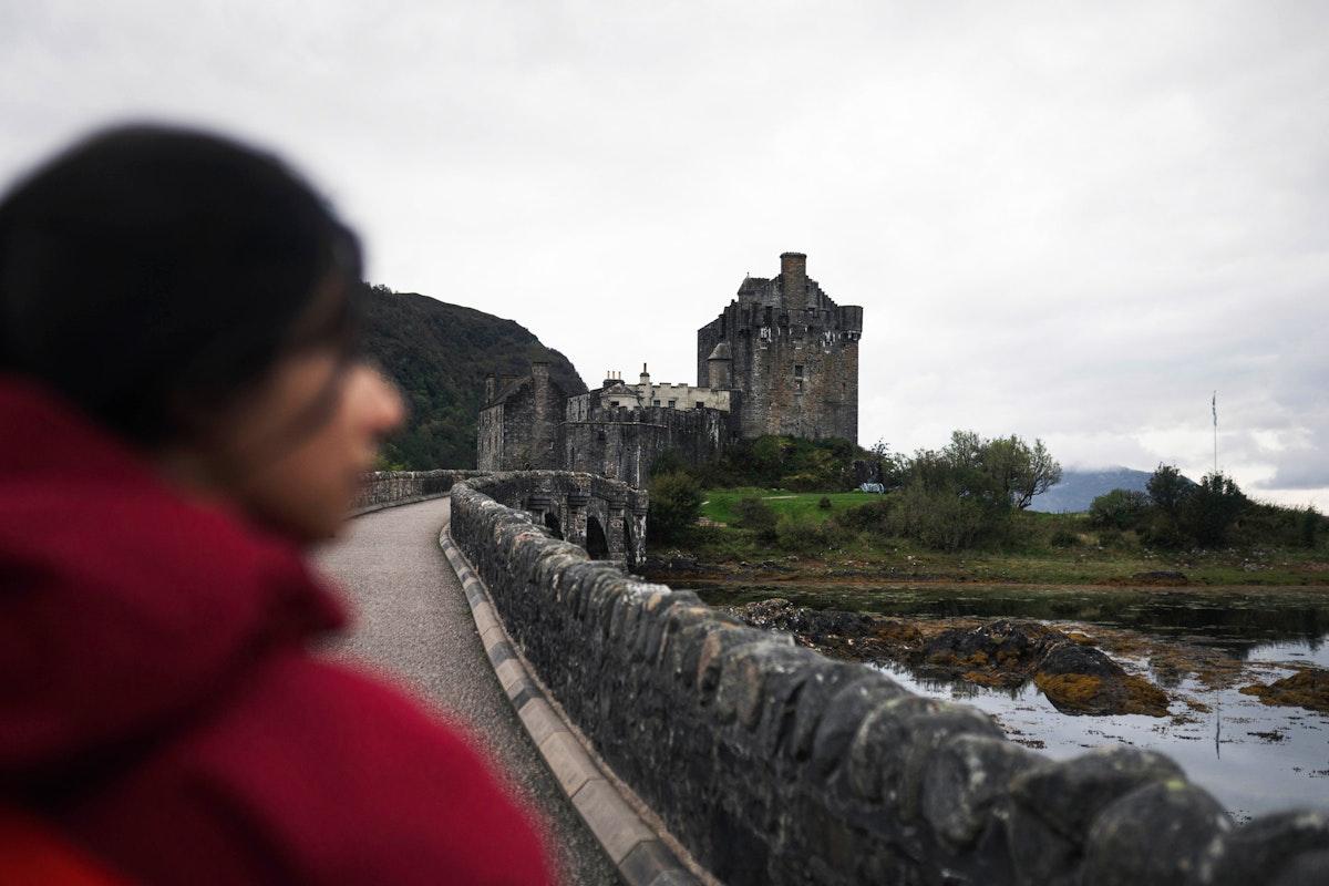 Female traveler on a bridge at Eilean Donan Castle, Scotland