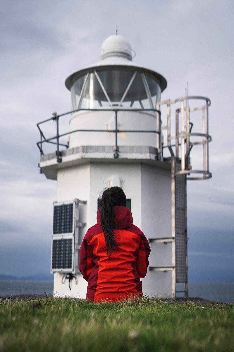 Female traveler at Vaternish Lighthouse on Isle of Skye, Scotland