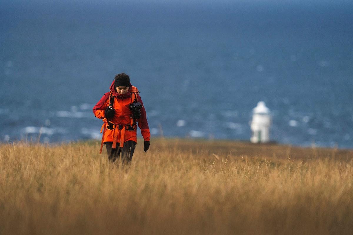 Female photographer at Vaternish Lighthouse on Isle of Skye, Scotland