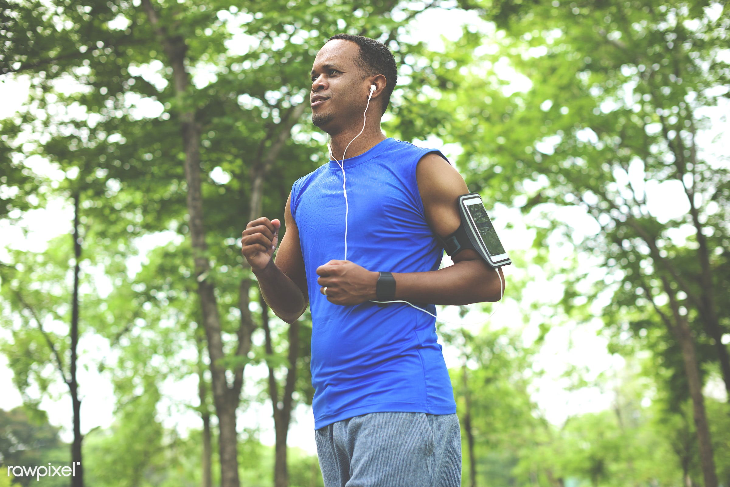 Guy running while listening to music on his mobile - african, african descent, cheerful, clothing, exercise, exercising,...