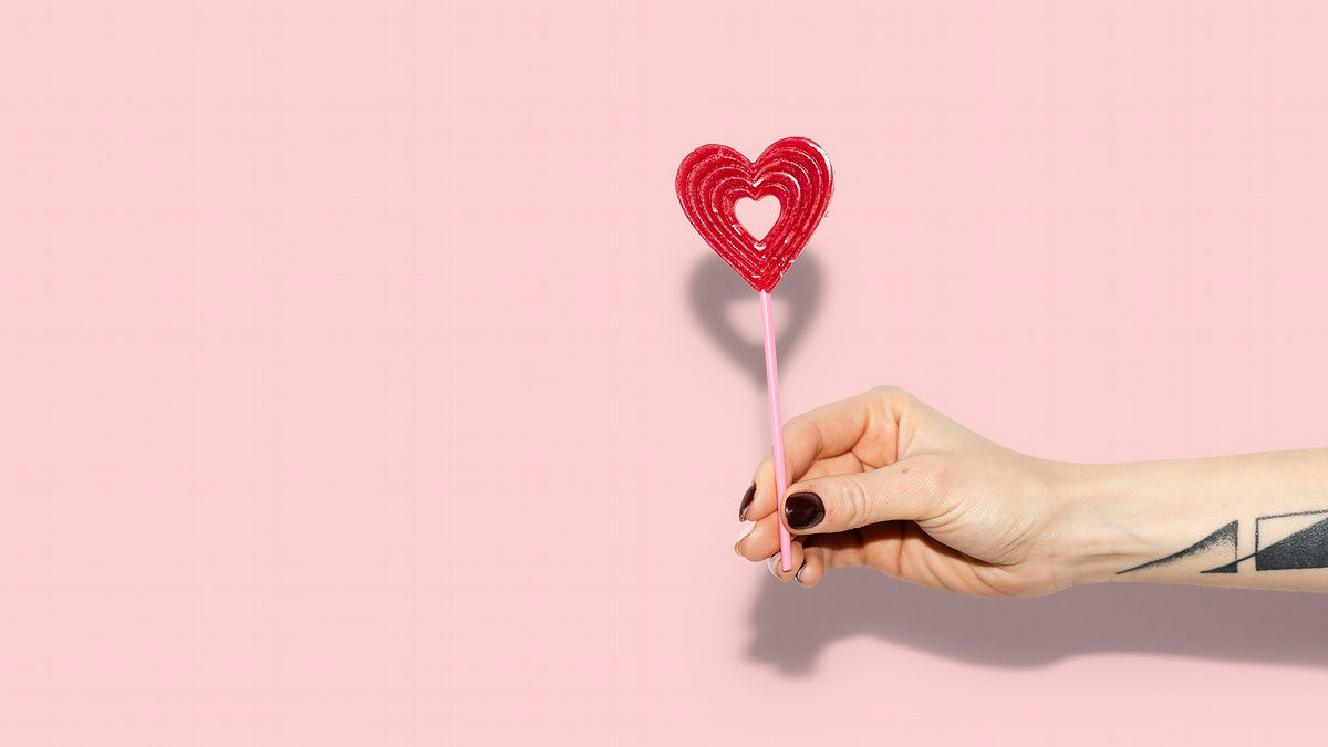 Woman holding a red heart on a stick wallpaper