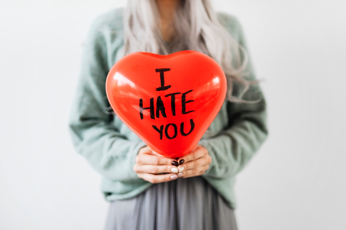 Woman showing a heart red balloon with I hate you on it