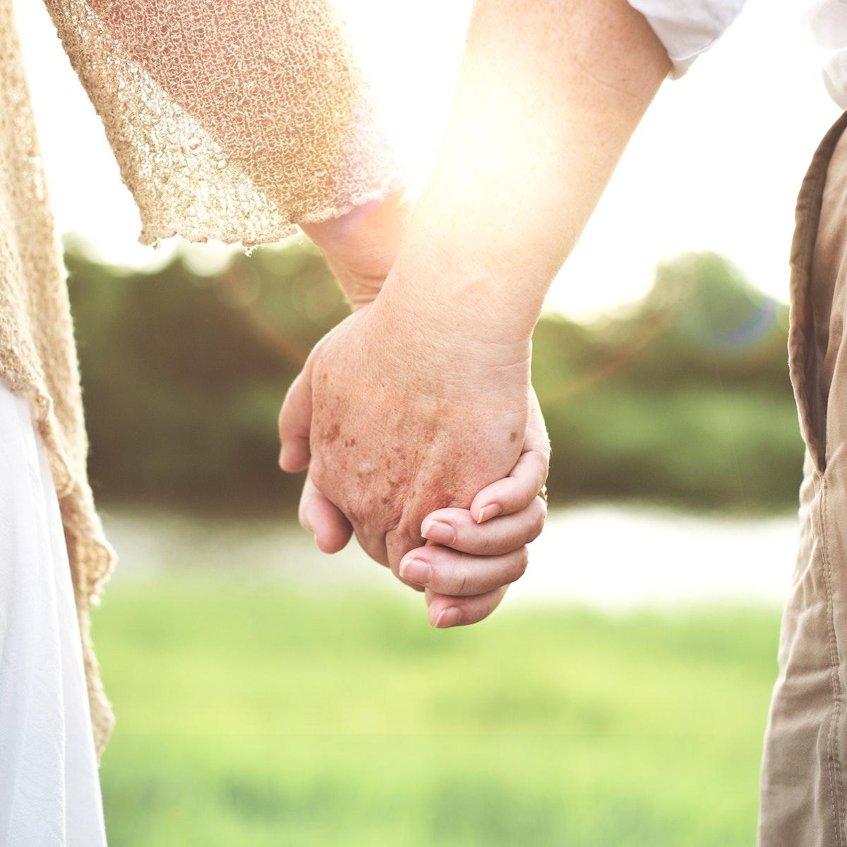 Closeup of seniors holding hands outdoors