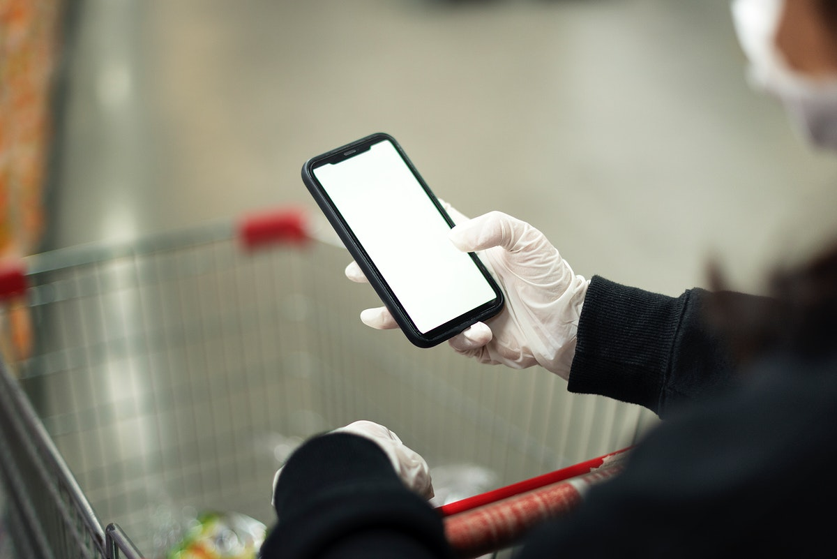 Woman wearing a latex glove while using cellphone to prevent coronavirus contamination