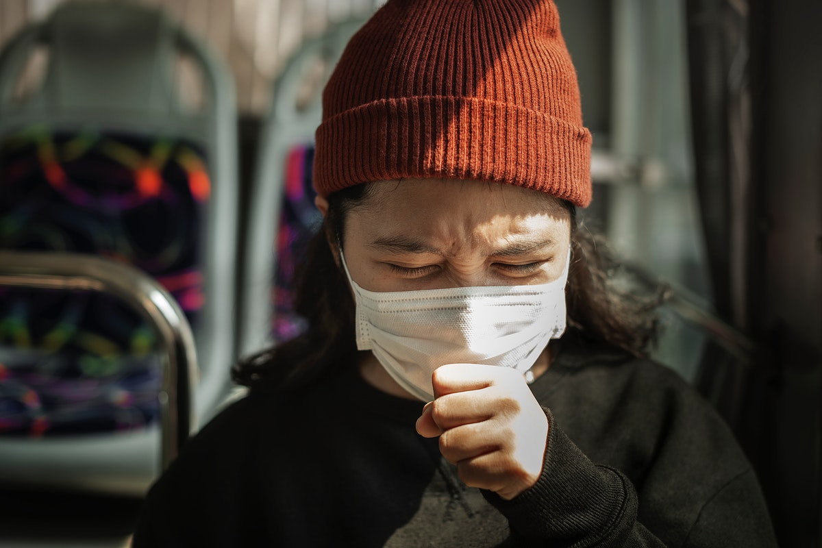 Sick woman in a mask coughing in public during coronavirus pandemic