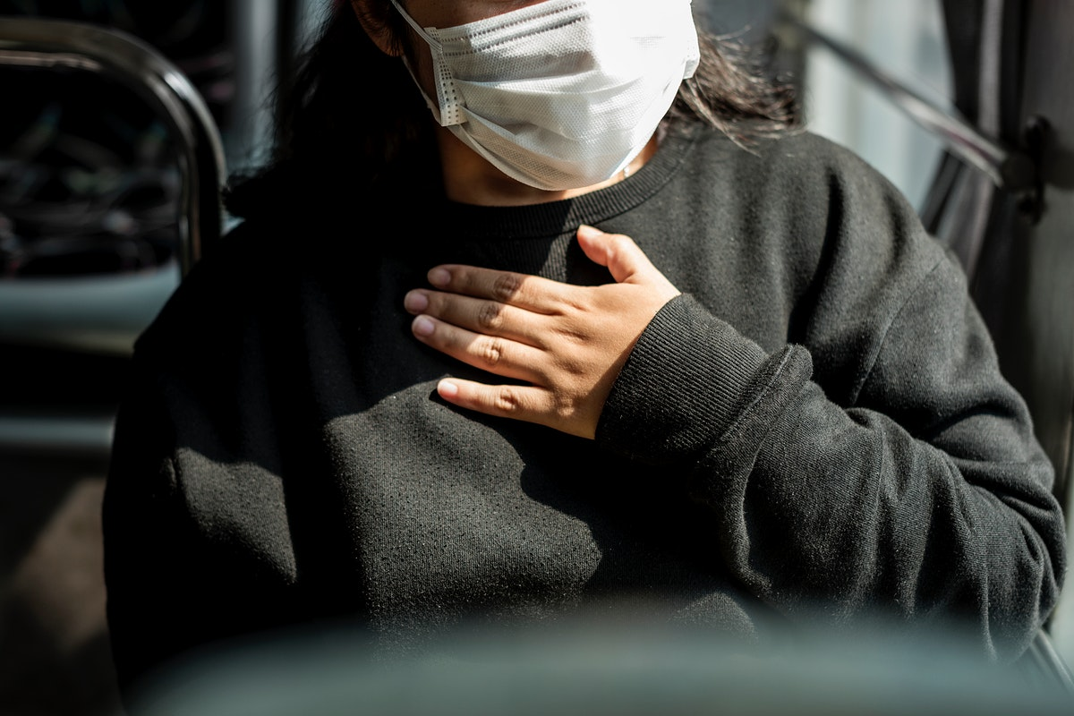 Sick woman in a mask having a difficulty breathing during coronavirus pandemic