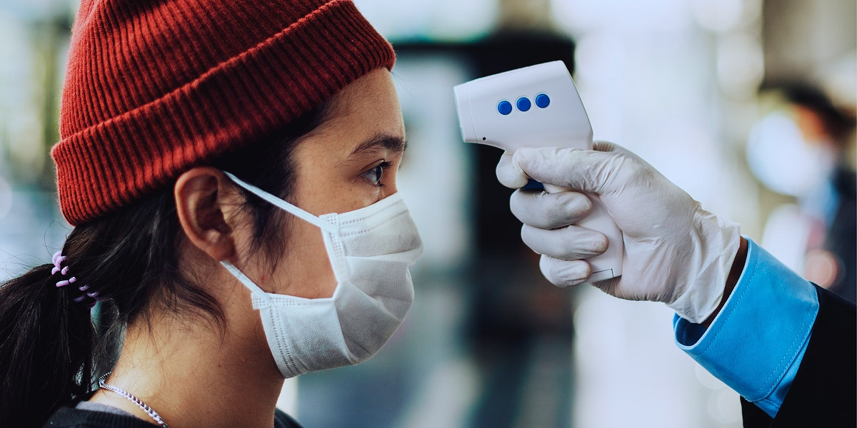 Woman in a medical mask getting her temperature measured by an electronic thermometer coronavirus banner