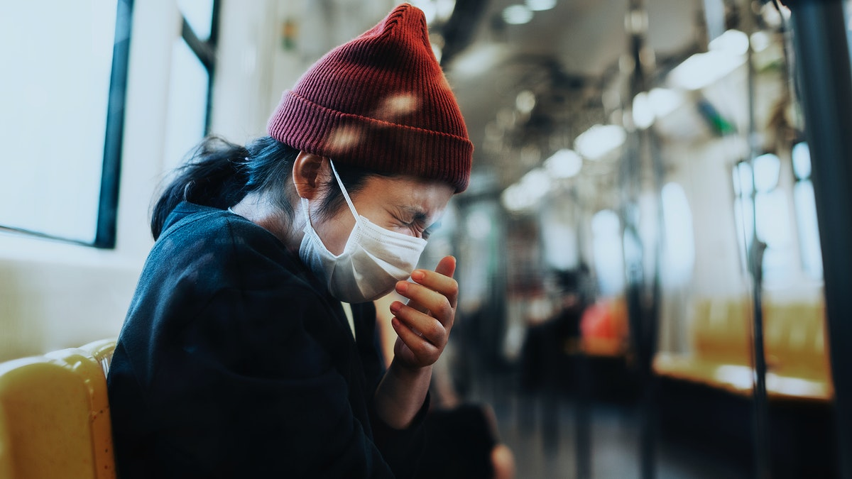 Sick woman in a mask sneezing in a train during coronavirus pandemic