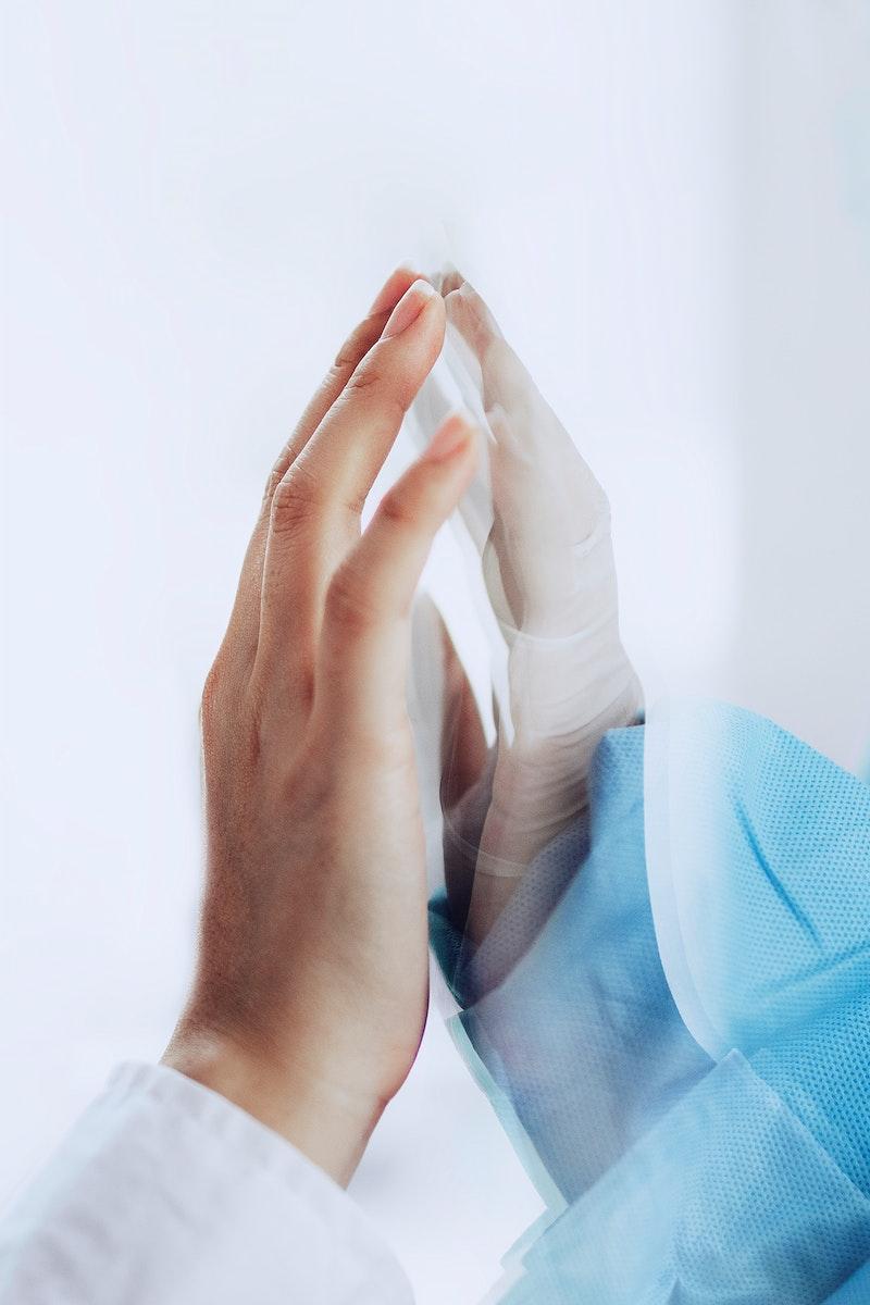 Coronavirus doctor touching family hand through a glass window