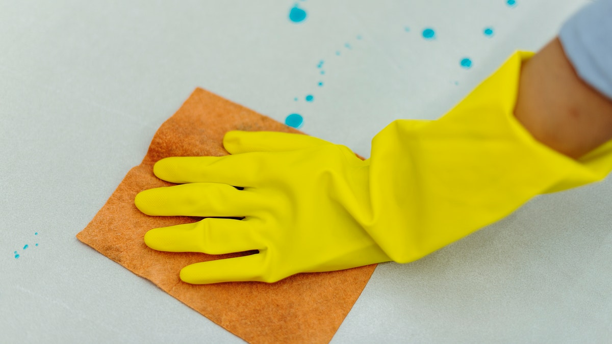 Woman wearing yellow rubber gloves and cleaning the surface