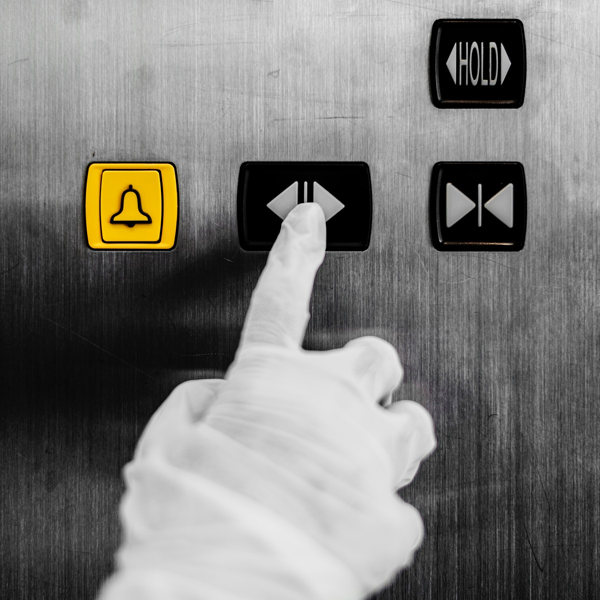 Gloved hand pressing an elevator button to prevent coronavirus contamination