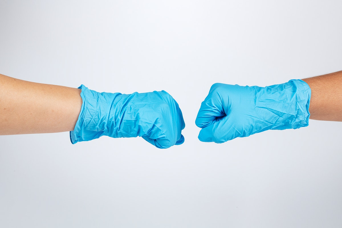 Medical staff bumping fists to support each other during coronavirus pandemic