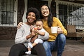 Happy diverse family sitting at the porch during covid19 lockdown