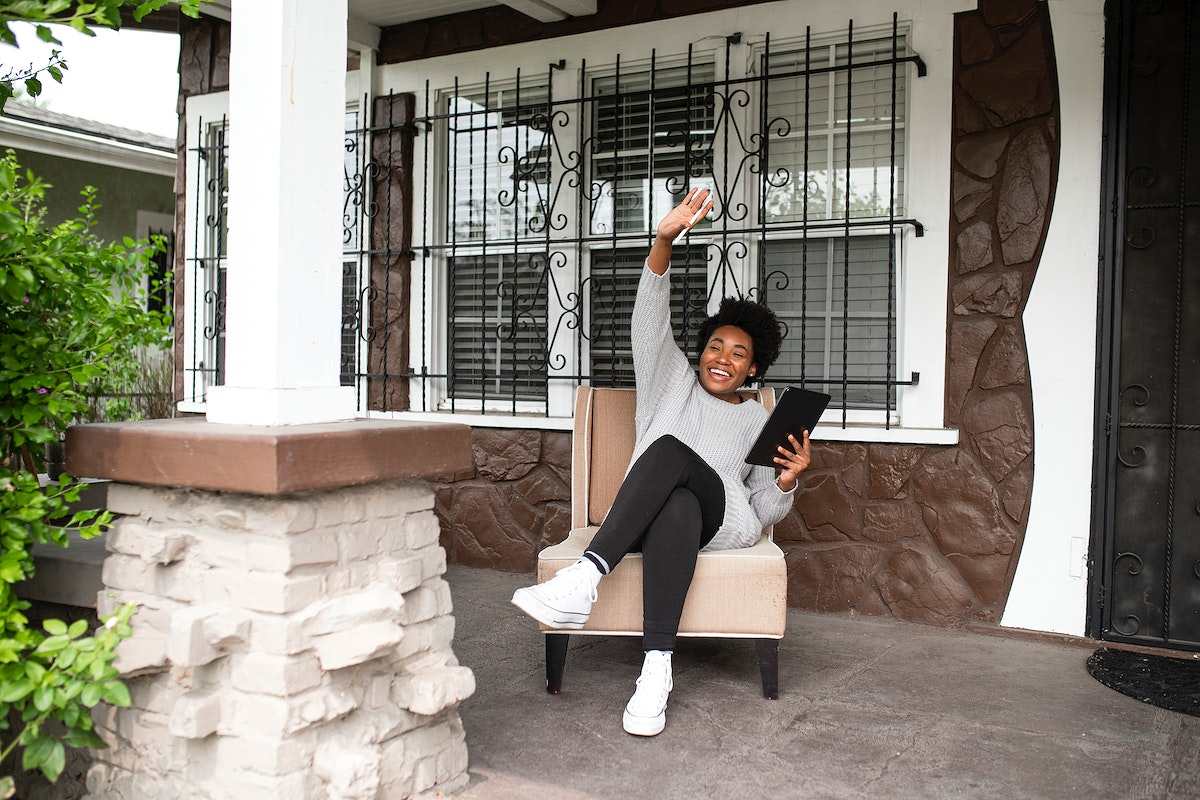 African American woman waving to a neighbor