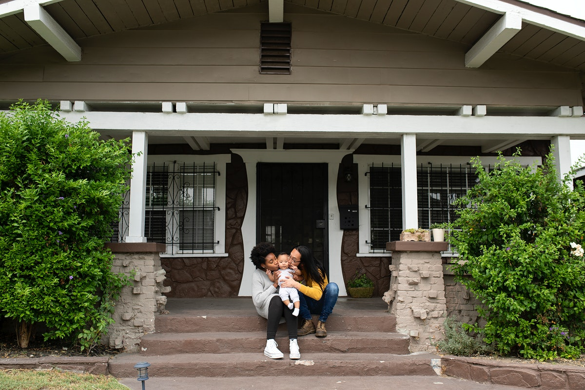 Happy multiracial parents kissing their son in front of the house during covid19 lockdown