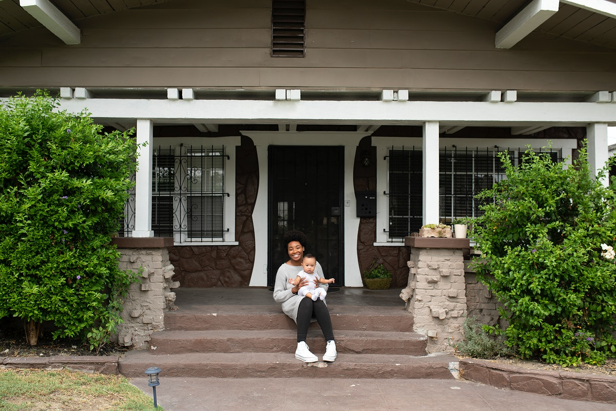 African American mother sitting with her son on the front porch