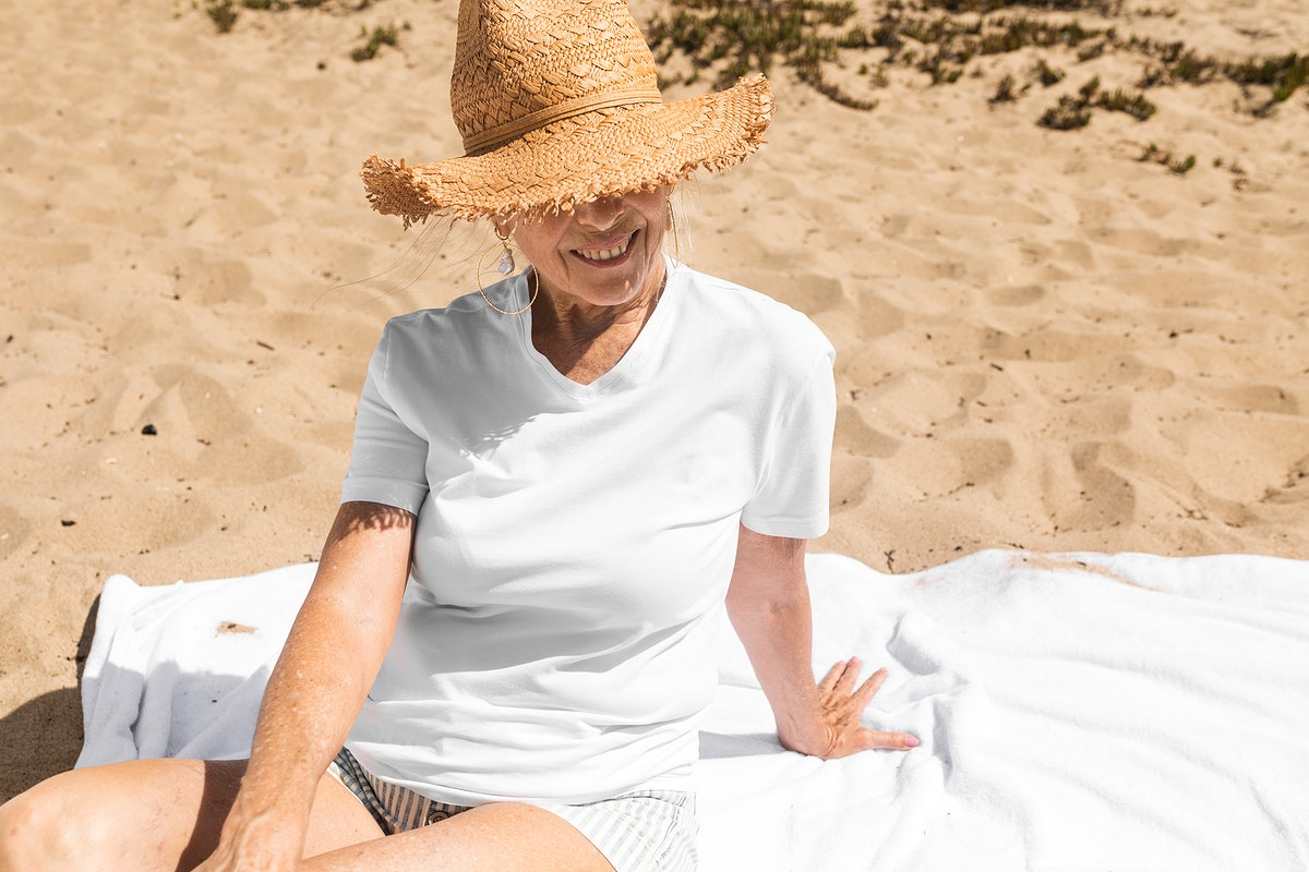 Senior woman in sun hat chilling at the beach