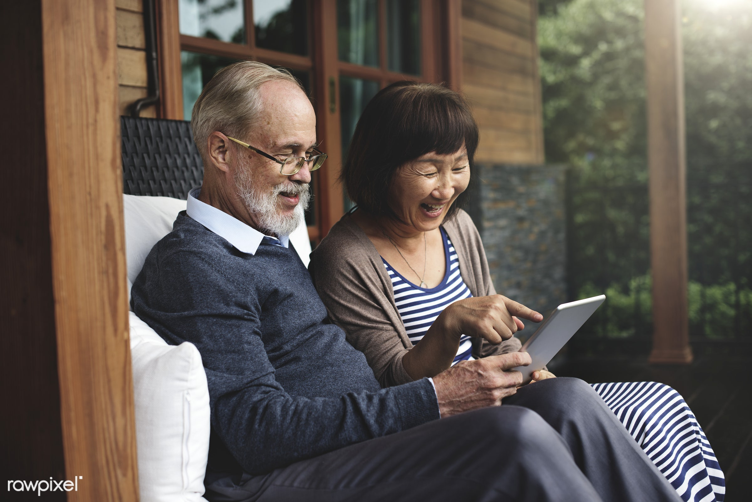 Senior couple using a tablet in the patio - adult, asian ethnicity, bonding, chair, cheerful, couple, dating, device,...