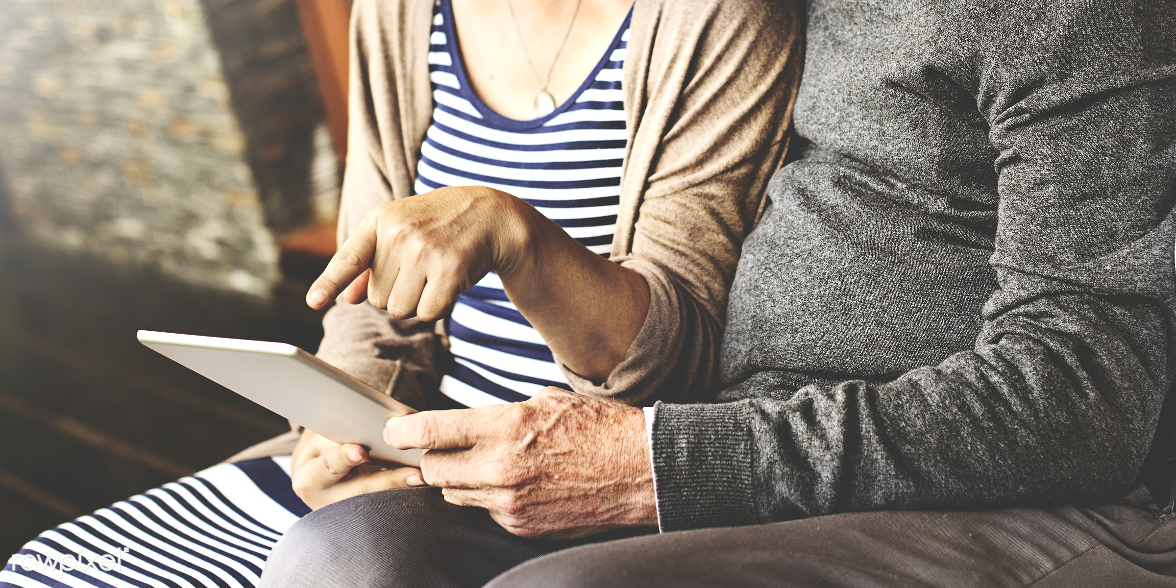 Senior couple using a tablet in the patio - adult, asian ethnicity, bonding, caucasian, chair, cheerful, couple, dating,...