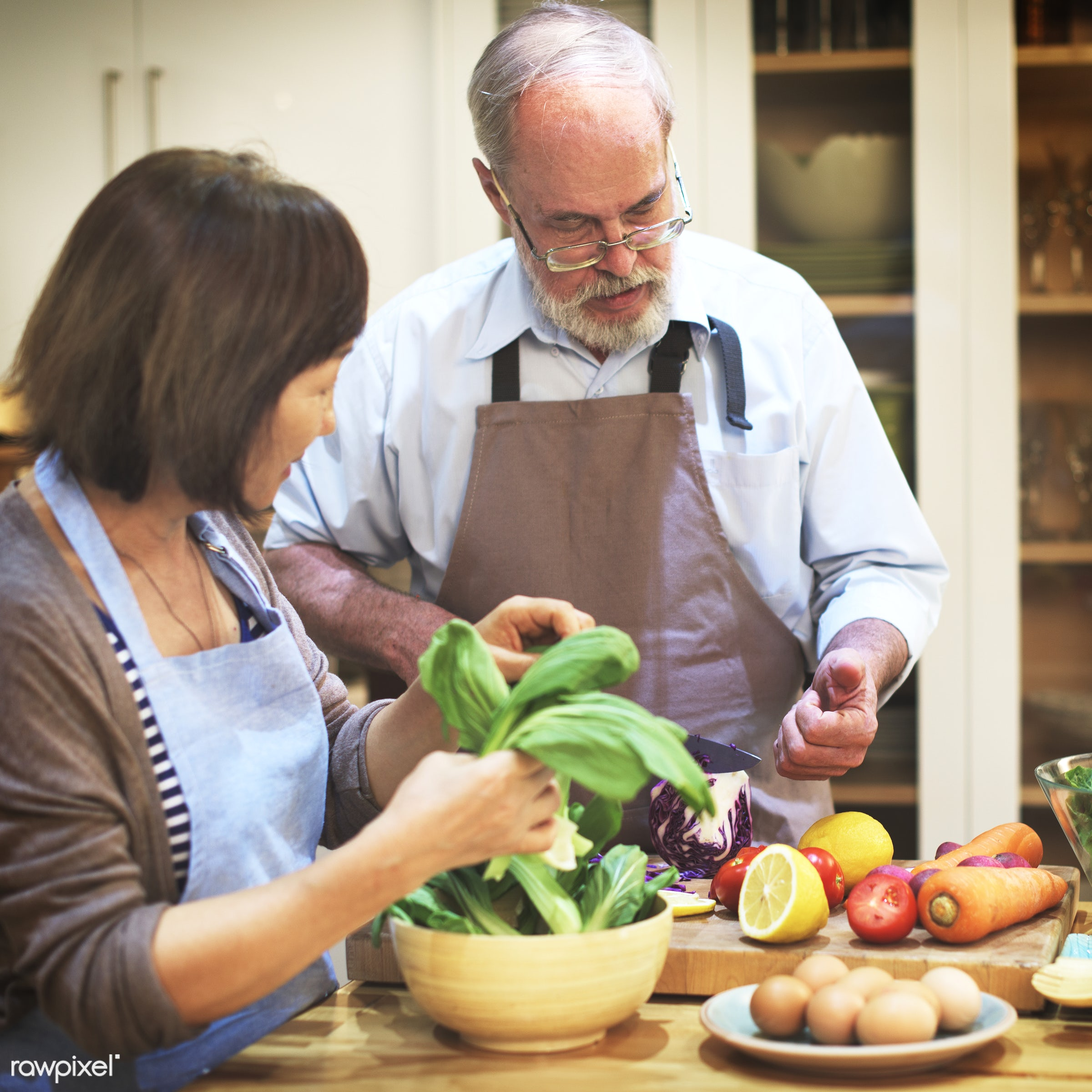 Interracial senior couple in a kitchen cooking healthy food together - cooking, couple, food, frying, home, housework,...