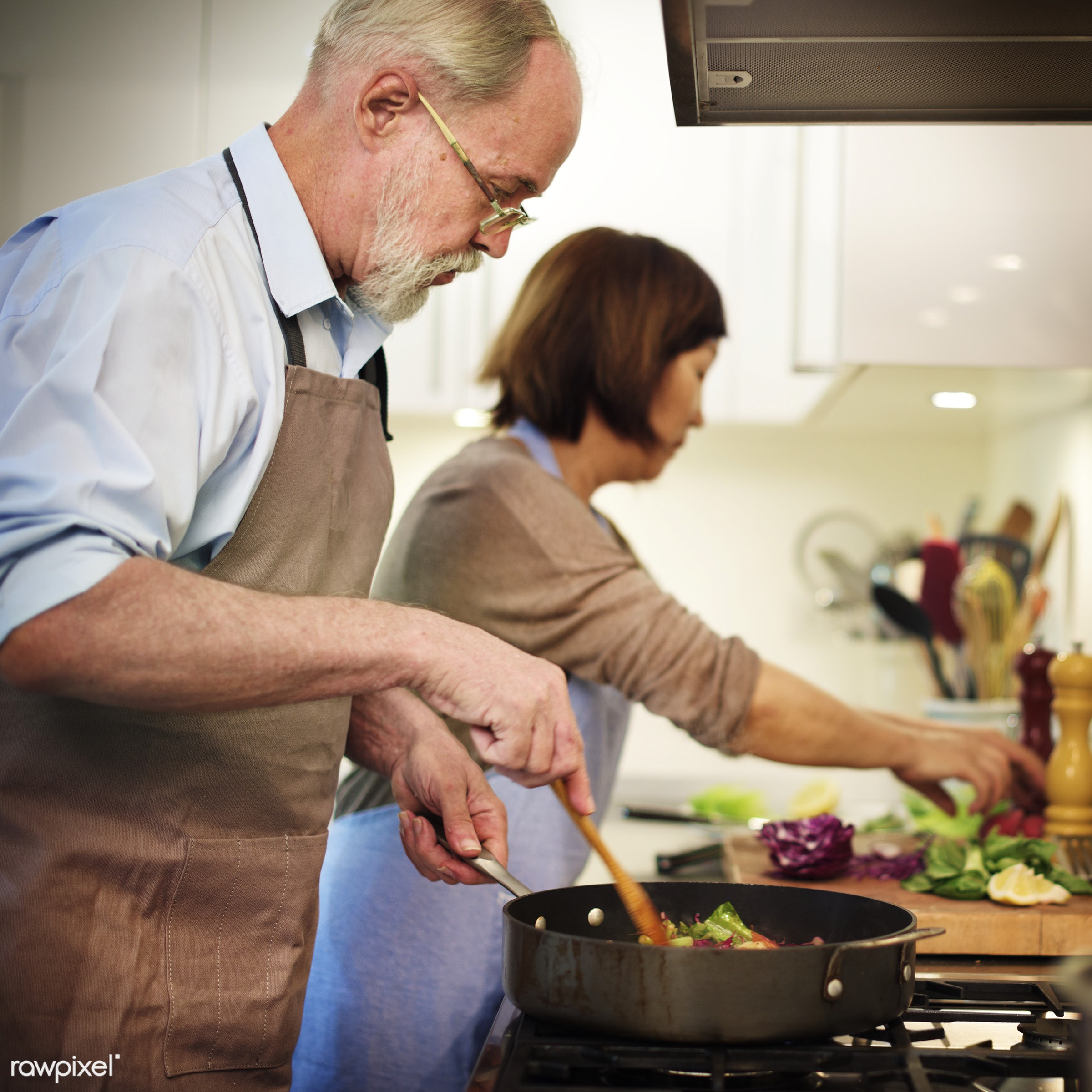 Senior couple cooking together in the kitchen - food, home, mature, cooking, couple, frying, housework, kitchen, old, senior...