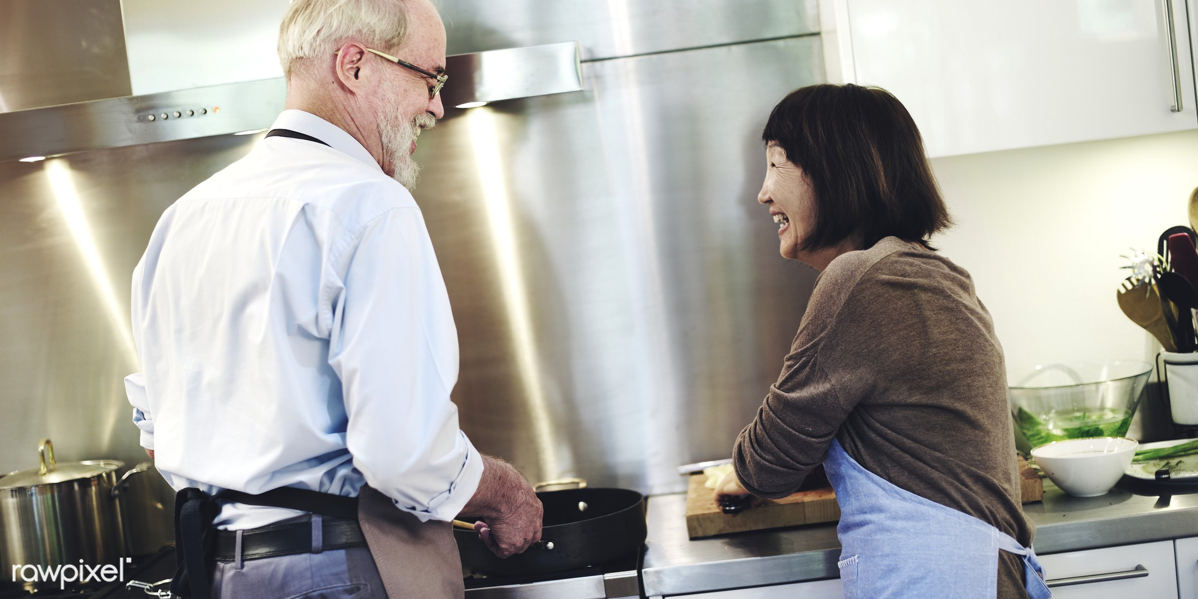 Senior couple cooking in the kitchen - activity, apron, asian, breakfast, care, caucasian, cheerful, chef, close,...