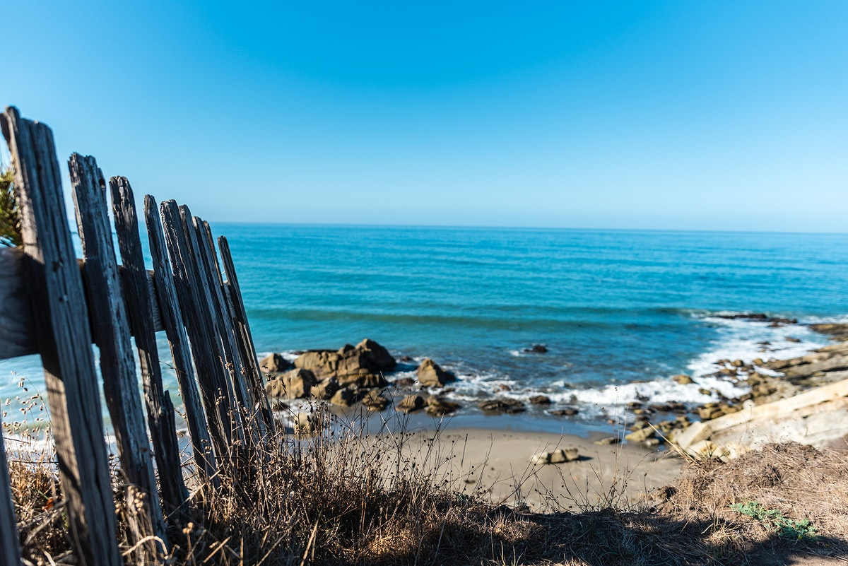 Wooden fence by a rocky beach