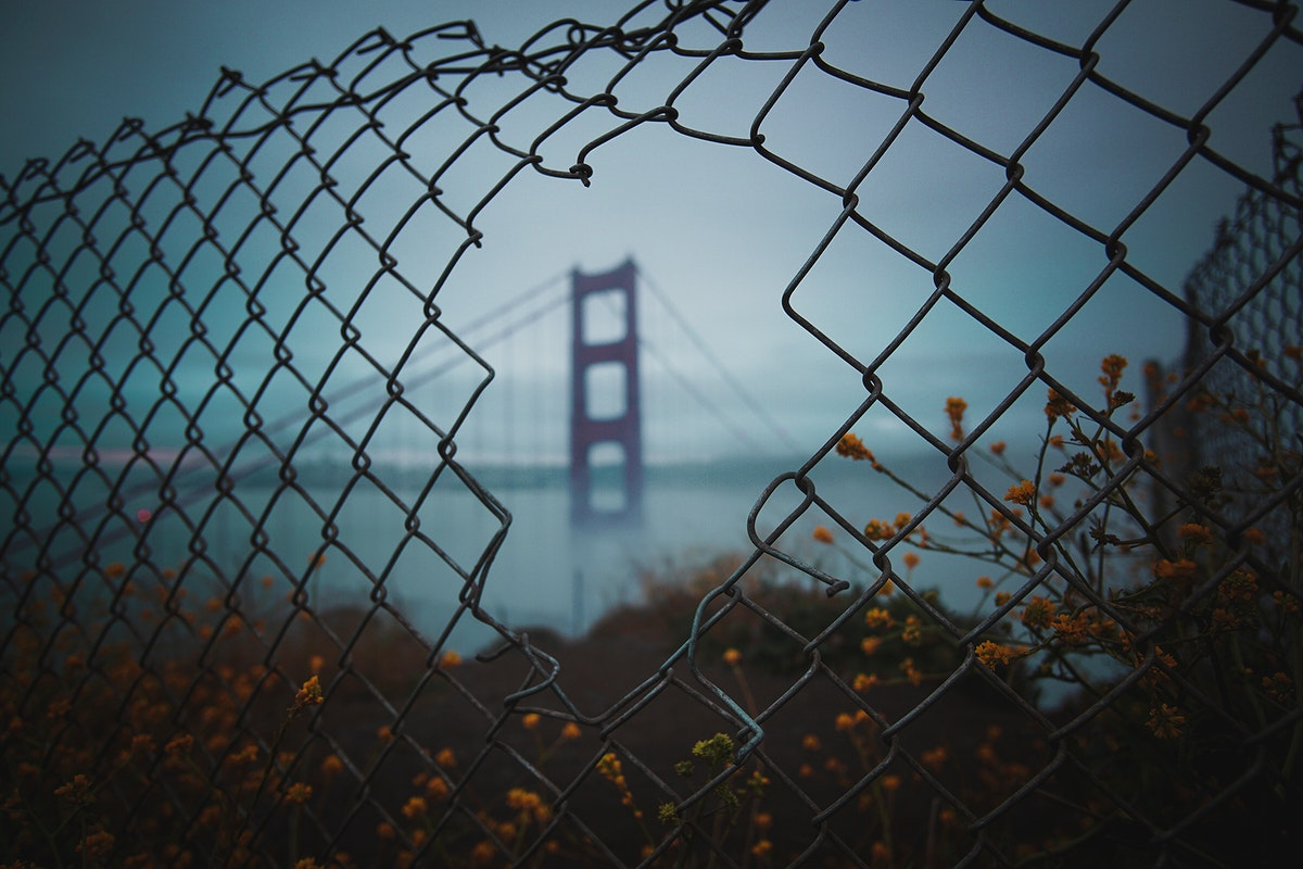 View of the Golden Gate Bridge, San Francisco, United States through a broken wire fence